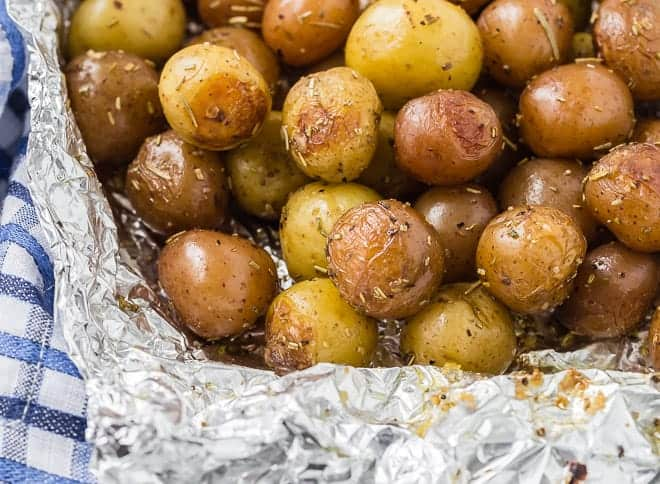 Landscape image of potatoes that have been grilled in a foil pack with rosemary.