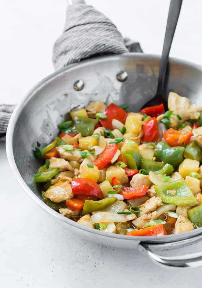 Chicken stir fry with sweet and sour sauce, pineapple, bell peppers, and onions in a wok.