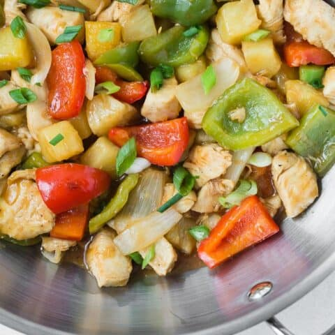 Close up view of chicken stir fry with pineapple, bell peppers, and onions in a wok.