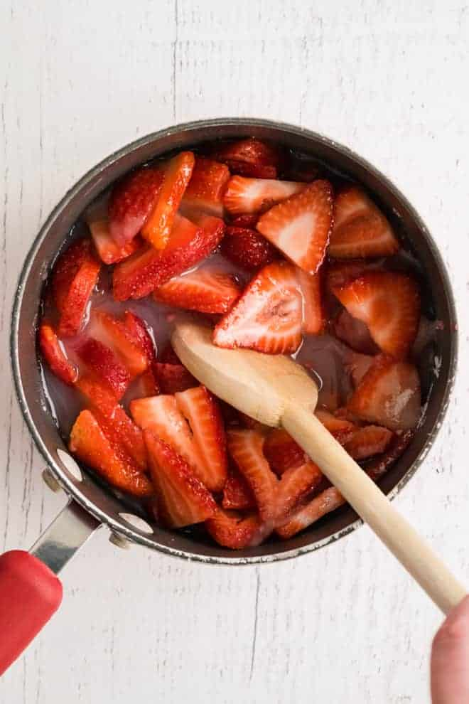 Overhead view of a sauce pan full of strawberries and red liquid, being stirred with a wooden spoon.