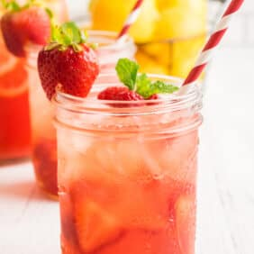 Sparkling berry pink lemonade in a mason jar with a red and white straw. Garnished with a strawberry and fresh mint.