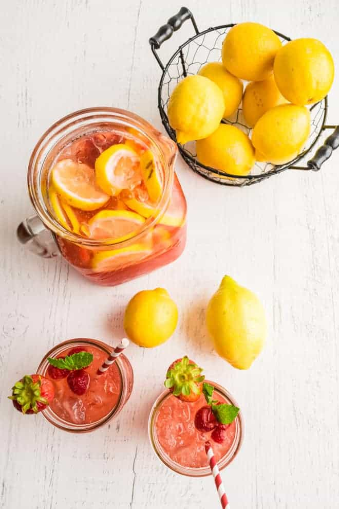 Overhead view of two glasses of pink lemonade, a pitcher, a bowl of lemons, and two lemons on a white wooden background.