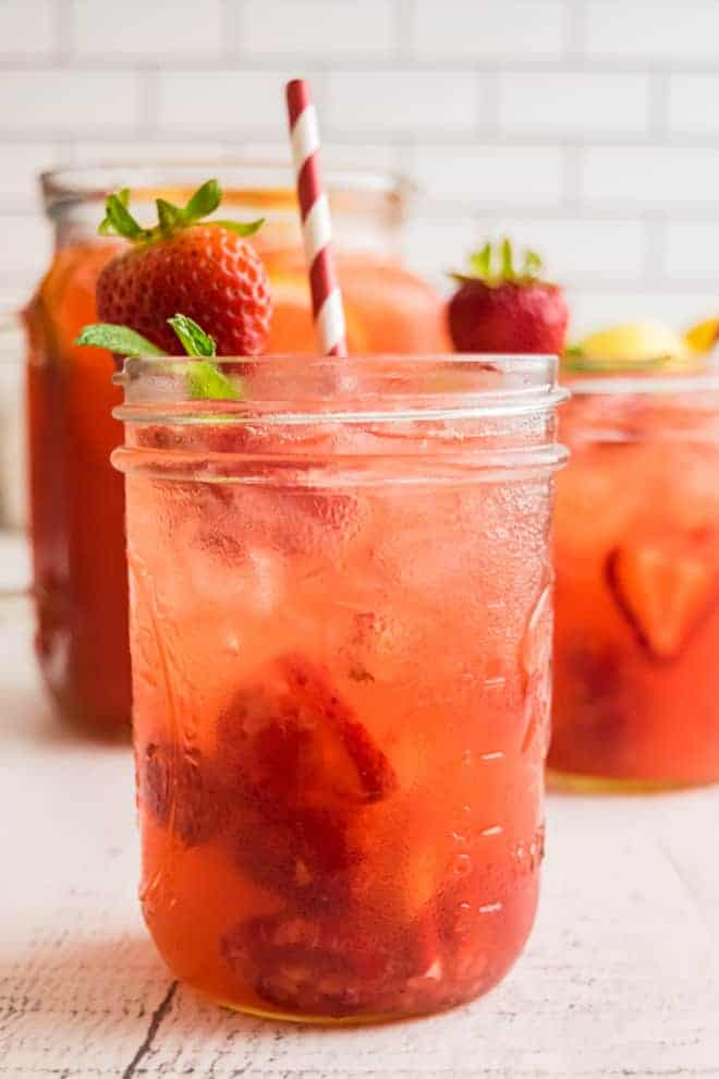 A light red drink on ice in a small mason jar. It is garnished with a fresh strawberry, mint leaves, and a red and white striped paper straw.