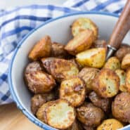 Crispy potatoes in a blue-rimmed white bowl, with a spoon in the bowl.