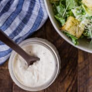 Overhead view of a jar of homemade caesar salad dressing, and a partially visible bowl of caesar salad.