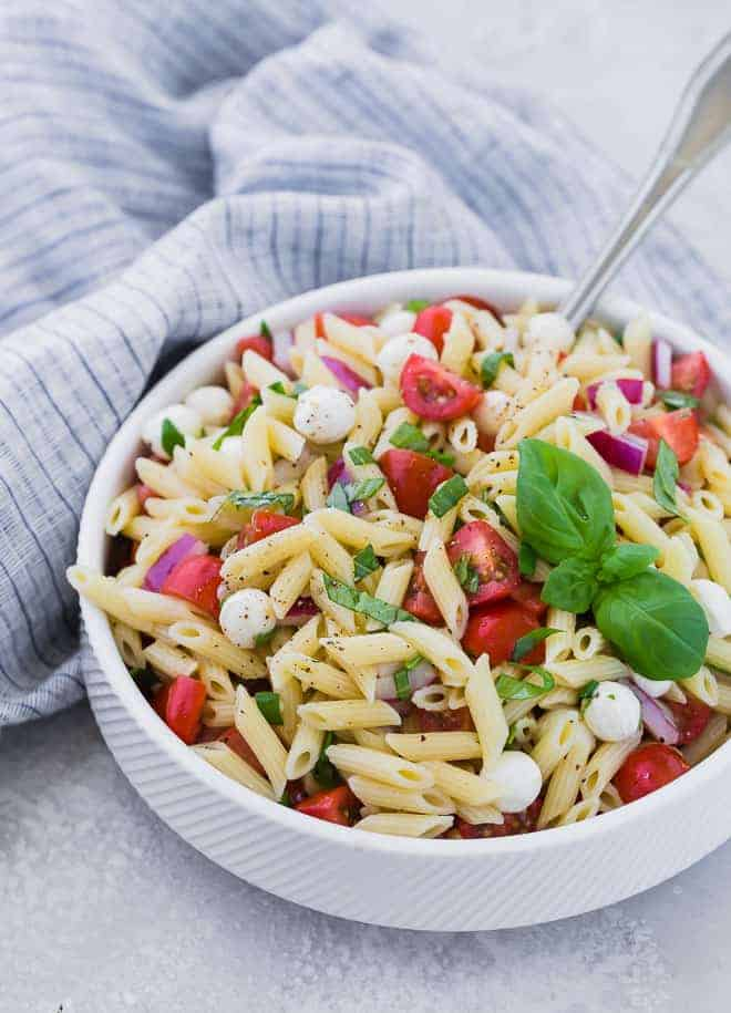 A white bowl full of mini penne pasta, grape tomatoes, pearl mozzarella, and fresh basil. A large silver serving spoon is also in the bowl.