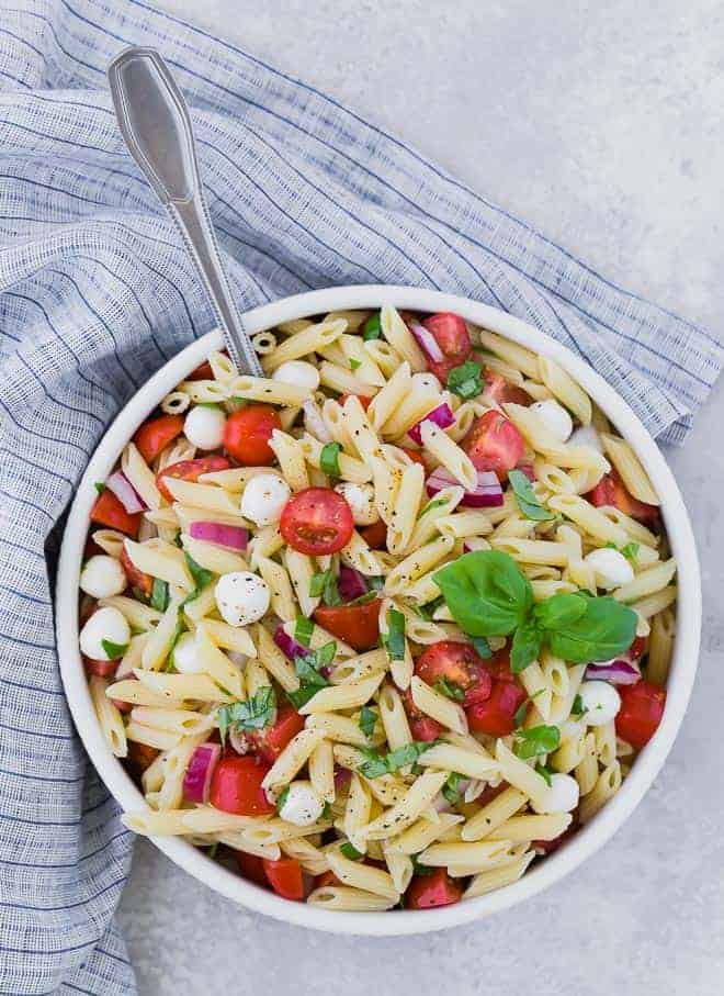Overhead view of a bowl of pasta salad with tomatoes, fresh mozzarella, red onion, and fresh basil.