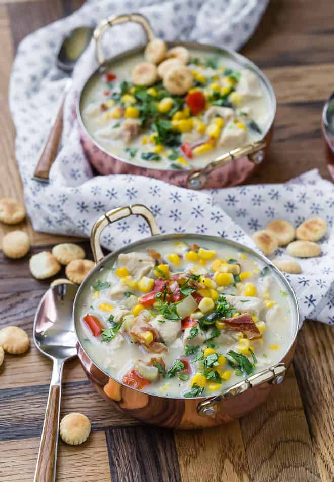 Corn chowder in a copper bowl, two bowls visible, with a blue and white linen and oyster crackers also pictured.