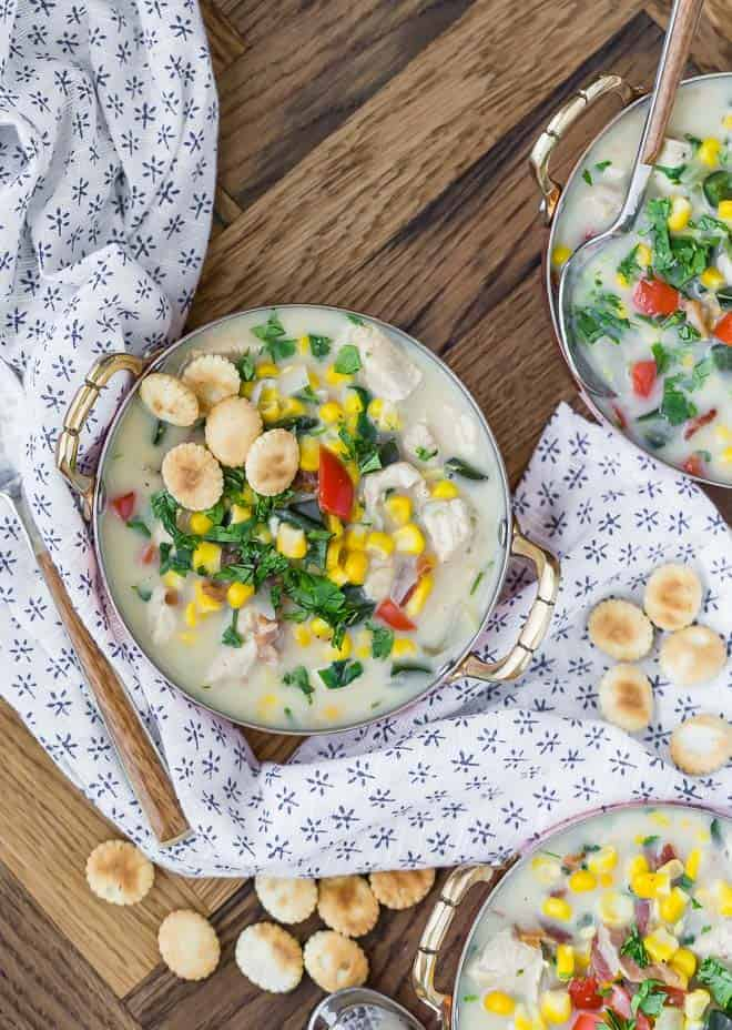 Overhead view of three bowls of chowder (only one fully visible). Chowder is topped with oyster crackers and fresh cilantro.