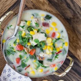 Close up overhead view of chicken corn chowder, in a two-handled bowl, with a spoon.