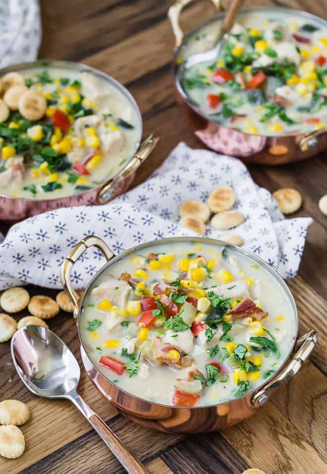 Three bowls of corn and chicken chowder. Spoons, oyster crackers, and lots of colorful vegetables are pictured.
