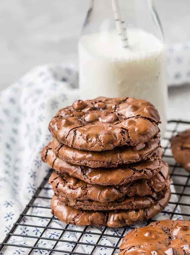 A stack of 5 rich chocolate cookies on a cooling rack with a small bottle of milk in the background.