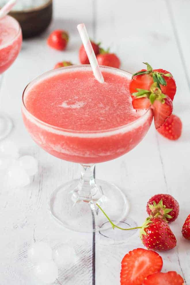 Frose in a stemmed glass, with. white and gold paper straw and fresh strawberry garnishes.