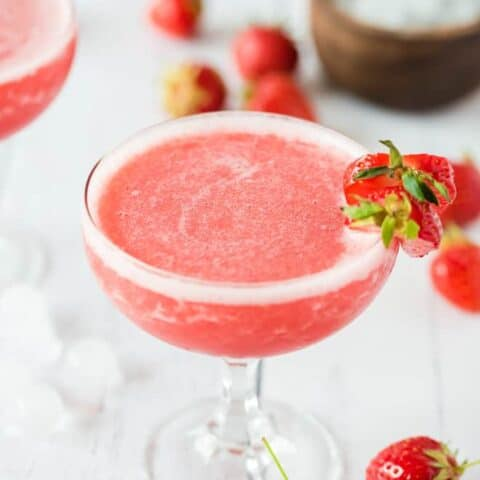 Frozen Rosé wine blended with strawberries in a stemmed glass, garnished with strawberries.