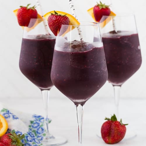 Three long stem wine glasses filled with frozen sangria, and topped with a fresh strawberry and orange slice. A paper straw is in each glass.