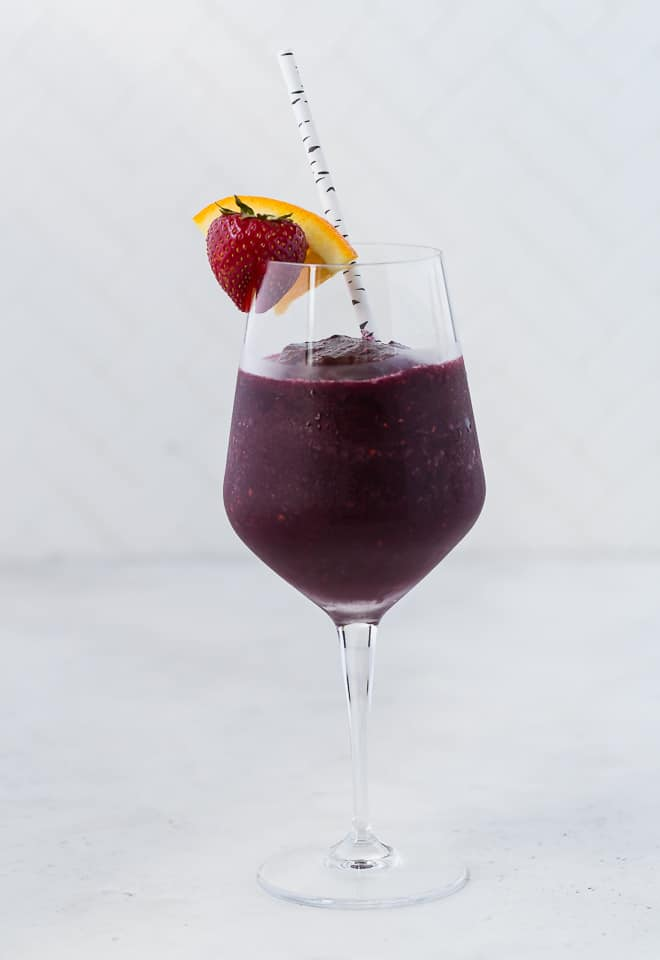 A long stem wine glass filled with a red wine sangria slushie, and topped with a fresh strawberry and orange slice. A paper straw is in the glass.