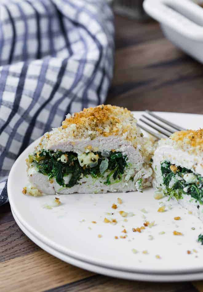 A baked chicken breast on a white plate, cut open to show a filling of spinach and feta cheese.