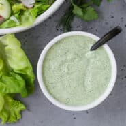 Overhead view of light green herby dressing in a small white bowl on a grey background.