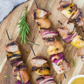 Overhead view of grilled pork, apple, and onion kabobs on a round wooden cutting board. A light orange sauce is also pictured in a small white bowl.