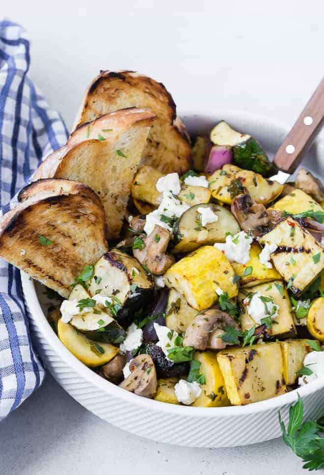 A white bowl filled with grilled zucchini, summer squash, mushrooms, and goat cheese. It is served with grilled bread pieces.