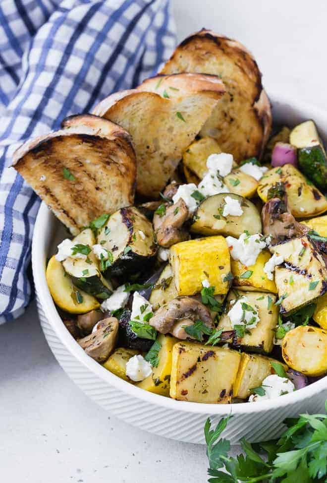 A white bowl on a light grey surface. Bowl is filled with grilled zucchini, summer squash, mushrooms, and goat cheese. It is served with grilled bread. A blue and white linen and fresh parsley is also pictured.