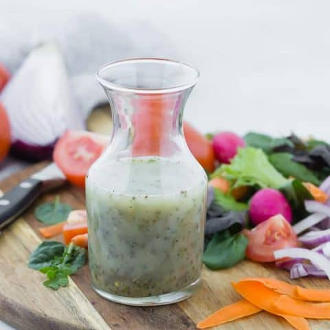 Small glass bottle of homemade italian dressing on wooden cutting board surrounded by colorful vegetables.