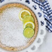 Overhead view of a tart on a white plate. The tart is topped with lots of powdered sugar, and lime and lemon wheels.
