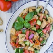 Overhead view of a panzanella salad on a large white and blue platter. Salad includes chopped tomatoes, cucumbers, fresh herbs, red onion, torn bread, and capers.