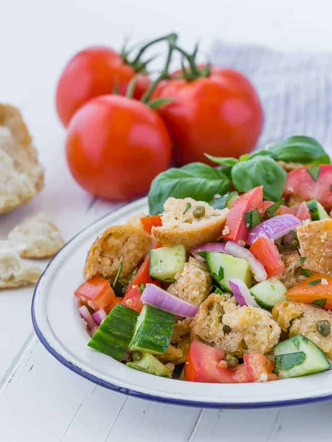 A summer salad on a large white and blue platter. Salad includes chopped tomatoes, cucumbers, fresh herbs, red onion, torn bread, and capers. Vine-ripened tomatoes and more torn bread are pictured in the background.