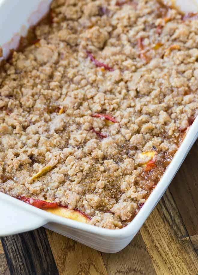 A crumble made with peaches in a white baking dish.