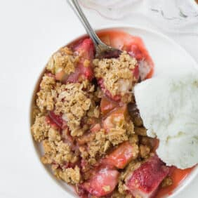 Close up view of strawberry rhubarb crisp and vanilla ice cream on a round plate, with a spoon.