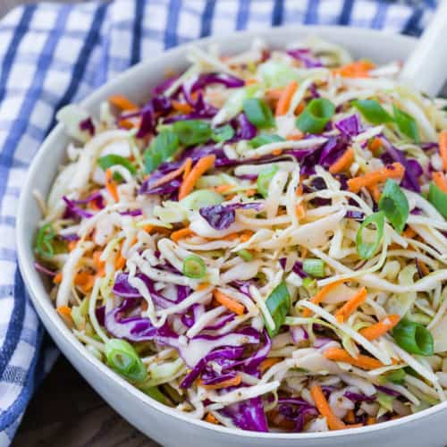 Shredded green and red cabbage, and carrots, in a white serving bowl. Salt and pepper shakers are visible in the background.