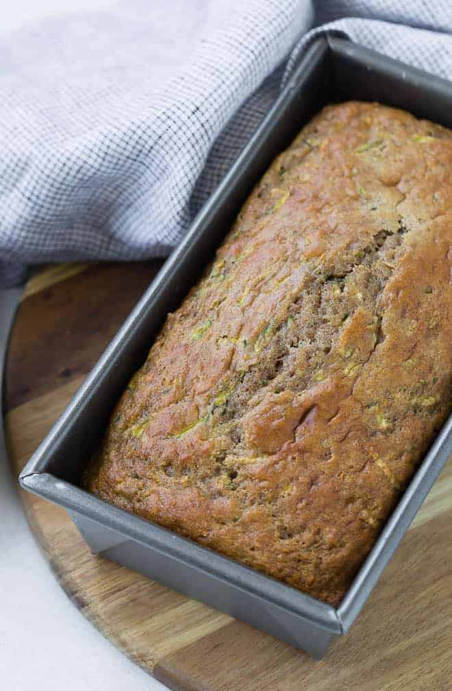 A silver loaf pan on a wooden surface, with a loaf of zucchini bread in the pan.