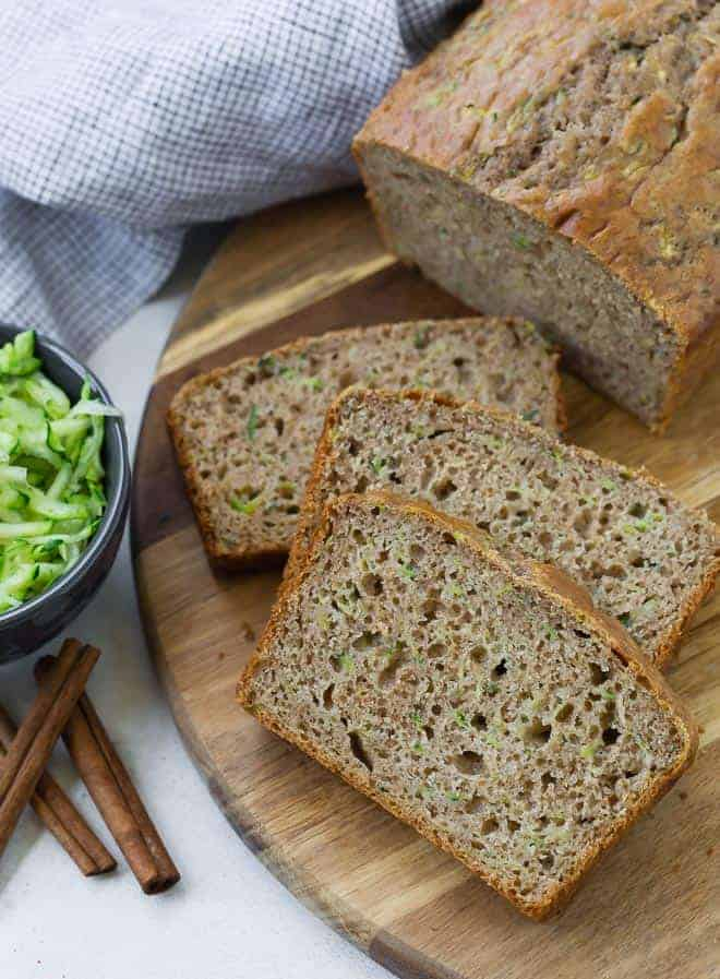 Sliced zucchini bread on a wooden surface. A small bowl of shredded zucchini sits next to the bread, as well as three cinnamon sticks.
