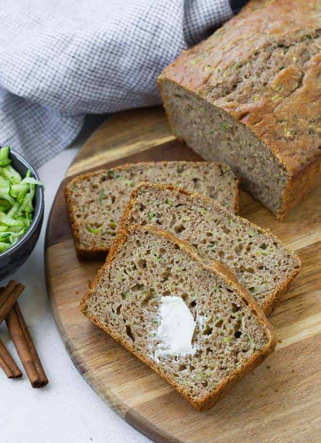 Sliced zucchini bread on a wooden surface. The top slice has a dab of butter on it.