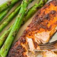 Salmon on a plate, being flaked with a fork. Sauteed asparagus is also pictured.
