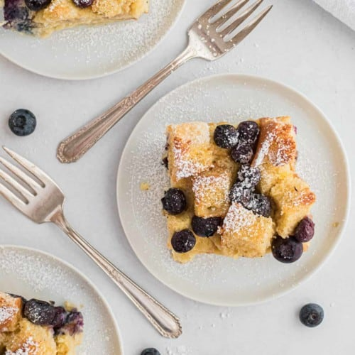 Overhead view of three slices of blueberry bread pudding on round white plates. Forks and fresh blueberries are also pictured.