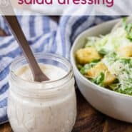 "A jar of caesar salad dressing in front of a tossed salad. A text overlay reads ""healthy caesar salad dressing."""