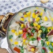 """Overhead view of creamy soup in a bowl. Text overlay reads """"healthy chicken corn chowder"""""""
