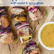 """Kabobs of pork chunks, apples, and onions sit on a wooden cutting board. A light orange dipping sauce is in a white bowl next to them. Text overlay reads, """"grilled pork & apple kabobs with sweet & spicy glaze."""""""
