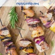 """Kabobs of pork chunks, apples, and onions sit on a wooden cutting board. A light orange dipping sauce is in a white bowl next to them. Text overlay reads, """"grilled pork & apple kabobs with apricot glaze."""""""