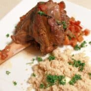 A white plate with a lamb shank, topped with a tomato based sauce and served with couscous, garnished with parsley.