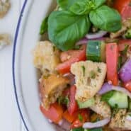 "Salad on a white plate, consisting of tomatoes, cucumbers, croutons, fresh herbs, and red onions. Text overlay reads ""How to Make Panzanella."""
