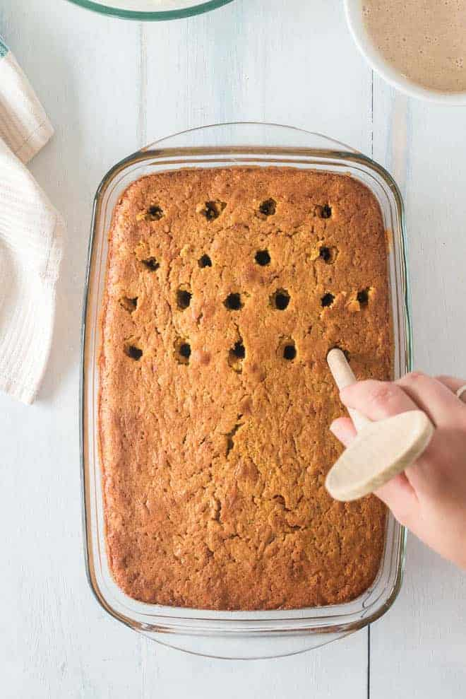 Holes being poked in a baked cake with a wooden spoon handle.