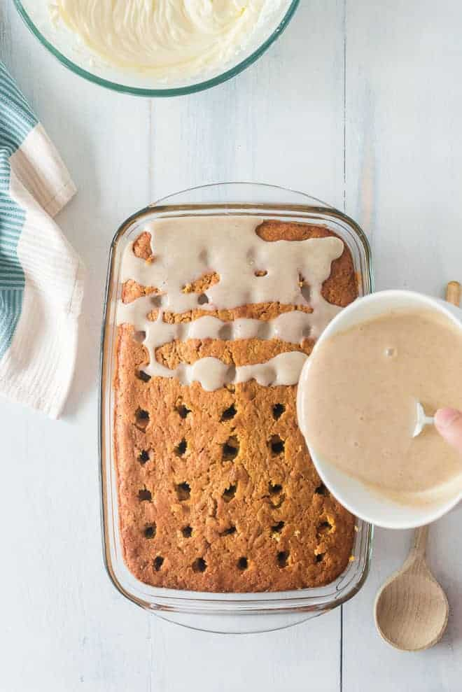 Sweetened condensed milk seasoned with cinnamon, being drizzled over a cake.