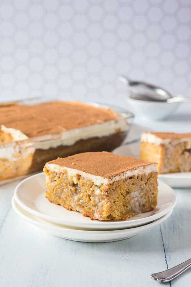 Pumpkin poke cake on a white plate, more cake in the background.