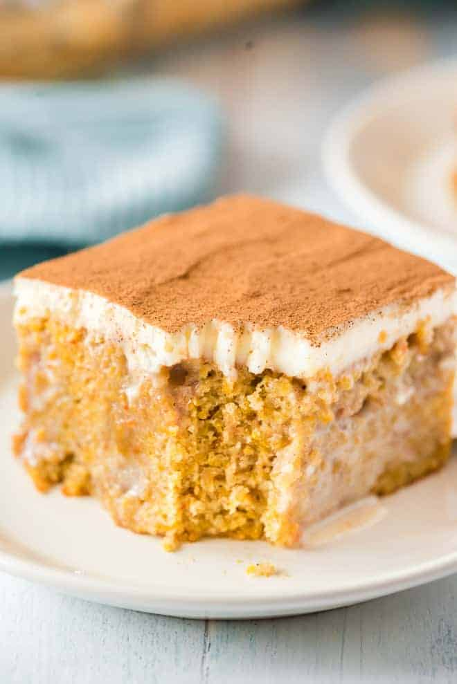 Close up of a slice of pumpkin cake, a bite has been taken out of it with a fork.
