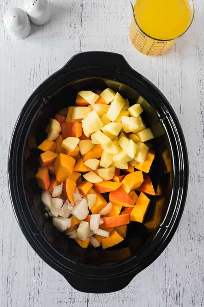 Cut up ingredients in a slow cooker: pumpkin, onions, potatoes.