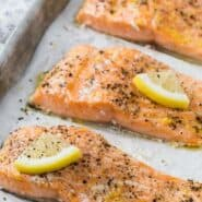 "Three salmon fillets on a parchment paper lined sheet pan. Each is topped with pepper and a lemon wedge. Text overlay reads ""slow roasted salmon, aka the juiciest salmon ever."""