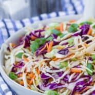 Colorful coleslaw in a white bowl with a blue and white linen.